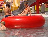 Kind mit großem Schwimmreifen im Bad