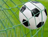 Ein Fußball fliegt ins Netz.