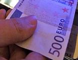 Euroschein wird in Glücksspielautomat gesteckt.