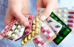 Frau hält verschiedene Medikamente in der Hand.