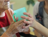 Betreuerin reicht Pflegeperson einen Becher