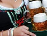 Kellnerin trägt Bier auf Tablett.