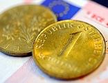 Zwei Schilling-Münzen liegen auf einem Zehn-Euro-Schein