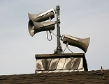 Drei Lautsprecher für Sirene auf einem Dach.