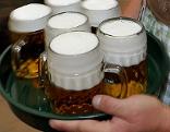 Kellner trägt Bier auf Tablett.