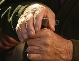 Alter Mann hält einen Gehstock