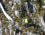 Paragleiter ist in Felswand gefangen und steht über dem Abgrund.