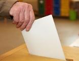 Mann wirft Wahlzettel in Wahlurne