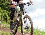 Mountainbikerin beim Downhill mit Protektoren ...