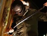 Einbrecher mit Werkzeug an Tür