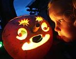 Kind blickt auf Kerzenlicht in ausgehöhlten Kürbis