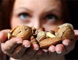 Frau hält verschiedene Nüsse in beiden Händen