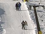 Skifahrer fahren mit Schlepplift