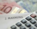 Taschenrechner, Euroscheine und Zettel mit Aufschrift : 2.Mahnung