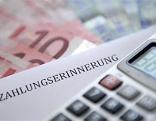 Taschenrechner, Euroscheine und Zettel mit Aufschrift: Zahlungserinnerung