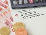 Lohnzettel mit Taschenrechner und Geld