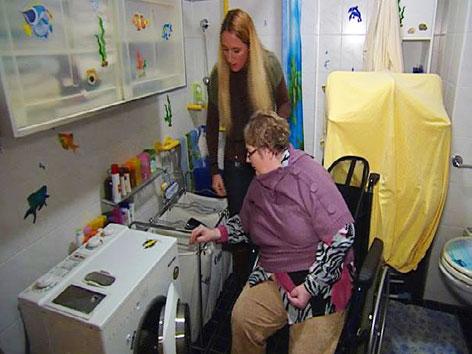 Klientin im Rollstuhl und Betreuerin füllen Schmutzwäsche in die Waschmaschine