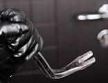 Hand in Lederhandschuh mit Brecheisen