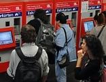 Menschen stehen vor Fahrkartenautomaten