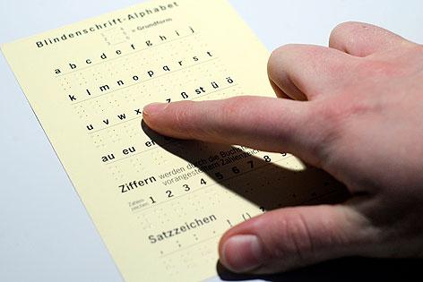 Frau liest mit Finger Blindenschrift