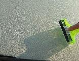 Eine Scheibe wird mit einem Eiskratzer enteist