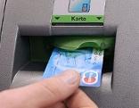 Mann steckt Bankomatkarte in  Geldautomaten