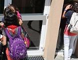 Kinder vor der Eingangstüre zur Schule