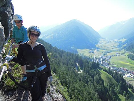 Zwei Kletterinnen am Klettersteig mit Blick auf St. Jodok im Tal