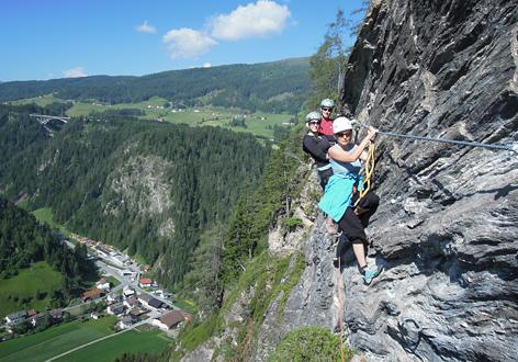 Drei Kletterer im Klettersteig mit Blick auf Stafflach im Tal unten
