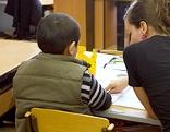 Junge Frau erklärt einem Schüler eine Aufgabe