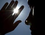 Frau hält Hand vor die Sonne