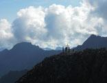 Das Gipfelkreuz des Aperen Turm, dahinter weiße Wolken.