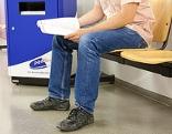 Arbeitslose Person sitzt in einem Warteraum des AMS