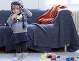 Kleines Mädchen mit Haube steht vor einer Couch