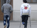 Zwei Asylwerber von hinten fotografiert, einer mit Krücken
