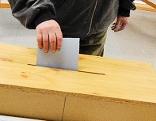 Mann wird Zettel in Wahlurne