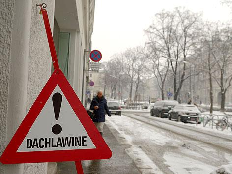 """Schild """"Dachlawine"""" auf Gehsteig vor verschneiter Straße"""