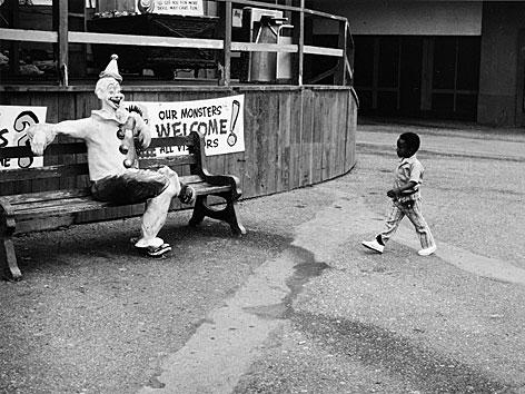 Fotografie von Roger Ballen: Ein kleiner schwarzer Junge läuft auf einen Clown zu