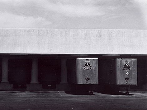 Ansicht einer Laderampe mit zwei Lkws. Foto von Lewis Baltz