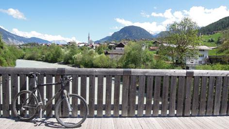 Rad lehnt an hölzernem Brückengeländer, im Hintergrund Roppen