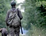 Jäger mit Jagdhund im Wald