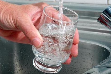 Wasserglas wird unter Wasserhahn gehalten