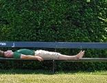 Mann liegt auf Parkbank