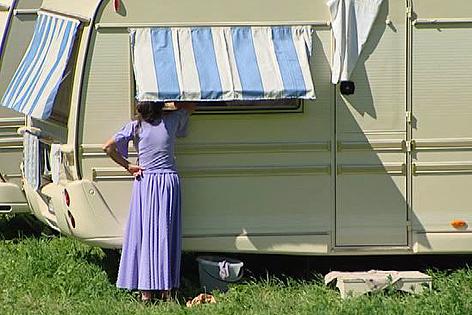 Frau vor Wohnwagen