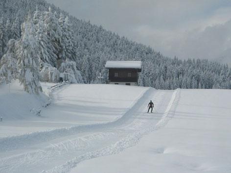 Langläufer auf tiefverschneiter Loipe