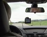 Autolenker mit Navigationsgerät an Windschutzscheibe