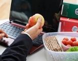 Man sitzt vor Laptop mit Apfel in der Hand