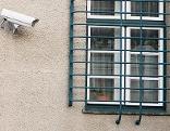 Überwachungskamera und vergittertes Fenster