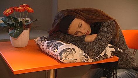 Frau schläft mit Polster am Tisch