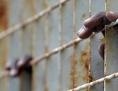 Finger eines Flüchtlings am Gitter eines Aufnahmezentrums auf Lampedusa
